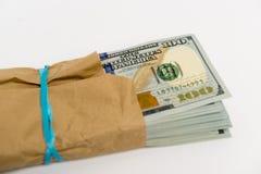 Bunt av dollarsedlar och det bruna kuvertet Royaltyfria Foton