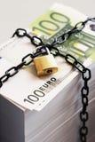 Bunt av euro som säkras av hänglåset och kedjan Arkivfoto