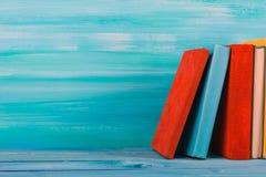 Bunt av färgrika böcker, grungy blå bakgrund, utrymme för fri kopia Royaltyfri Foto