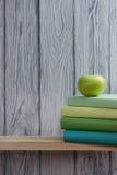 Bunt av färgrika böcker och det gröna äpplet på trätabellen tillbaka skola till kopiera avstånd arkivbilder