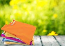 Bunt av färgrika t-skjortor på trätabellen med royaltyfria bilder