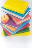 Bunt av färgrika verkliga böcker, äpple på vit bakgrund, partisk sikt Dra tillbaka till skolan, kopieringsutrymme Utbildning Arkivbilder