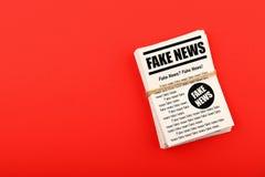 Bunt av FAKE NYHETERNAtidningar över rött royaltyfri bild