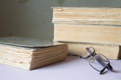 Bunt av gamla böcker med ett par av exponeringsglas Royaltyfri Foto