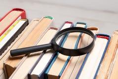 Bunt av gamla inbunden bokböcker med förstoringsglaset Sök för relevant och nödvändig information i ett stort antal källduri royaltyfri bild