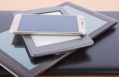 Bunt av grejer på ett skrivbord - anteckningsbok, minnestavla, ebookavläsare och royaltyfria bilder