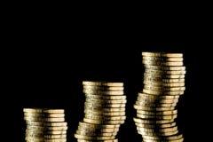 Bunt av guld- mynt p? en svart bakgrund arkivfoto