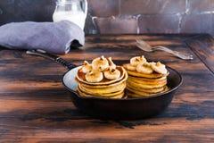 Bunt av hemlagade pannkakor med bananen, lönnsirap och valnötter i svart gjutjärnkastrull arkivfoto