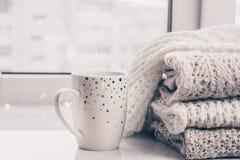 Bunt av hemtrevliga stickade plagg och en kopp kaffe på vitmarmorfönsterbräda mot vit fönsterbakgrund kopiera avstånd fotografering för bildbyråer
