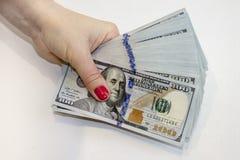 Bunt av hundra dollarsedlar i hand arkivbild