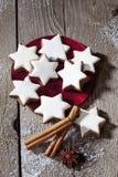 Bunt av kanelbruna stjärnor på plattan med för ans-stjärna för kanelbruna pinnar anis på trägolv Royaltyfri Fotografi