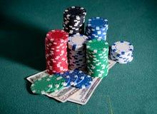 Bunt av kasinochiper och dollarräkningar på pokertabellen Arkivfoto