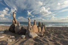 Bunt av kiselstenar som balanserar på en strand Arkivfoton