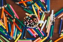 Bunt av kulöra blyertspennor i ett exponeringsglas arkivfoto