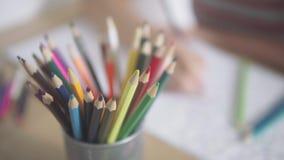 Bunt av kulöra penciles på tabellen Kameraglidbanor Färgvideo av en kvinnahand som rymmer en blyertspenna och färga stock video