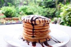 Bunt av läckra pannkakor med chokladsås på plattan på Royaltyfri Fotografi