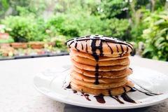 Bunt av läckra pannkakor med chokladsås på plattan på Royaltyfria Bilder