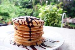 Bunt av läckra pannkakor med chokladsås på plattan på Arkivfoton