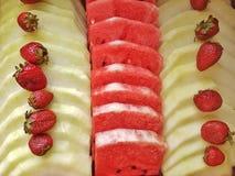 Bunt av många vattenmelonskivor, druvor och jordgubbar Fotografering för Bildbyråer