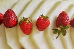 Bunt av många vattenmelonskivor, druvor och jordgubbar Arkivfoton
