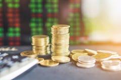 Bunt av mynt över suddighetsbakgrund av aktiemarknadskärmbakgrund arkivbild