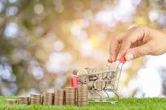 Bunt av mynt och mynt på shoppingvagnen Royaltyfri Fotografi