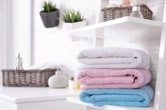 Bunt av nya färgglade handdukar på hylla i badrum arkivfoton