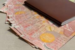 Bunt av Nya Zeeland 100 dollar sedel och röd räkningsimage Arkivfoton