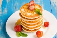 Bunt av pannkakastruvor med jordgubbar och honung på en pl arkivfoto
