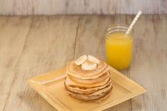 Bunt av pannkakor med bananer och ny orange fruktsaft Arkivbild