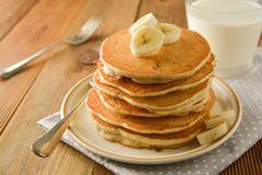 Bunt av pannkakor med bananskivor och honung, p? tr?bakgrund Hemlagade amerikanska pannkakor, royaltyfria foton