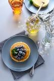 Bunt av pannkakor med det djupfrysta blåbäret och honung på grå bakgrund Selektivt fokusera arkivfoton