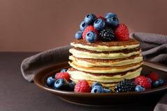 Bunt av pannkakor med det nya blåbäret, hallonet och björnbäret på den bruna plattan Arkivbild