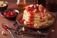 Bunt av pannkakor med jordgubbedriftstopp och valnötter smaklig efterrätt Arkivbild