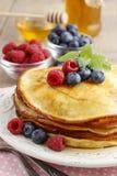 Bunt av pannkakor med sirap, hallon och blåbär Royaltyfria Foton