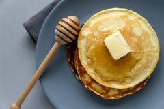 Bunt av pannkakor med smör och honung på grå bakgrund Selektivt fokusera Top beskådar arkivbilder