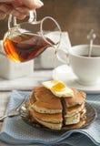 Bunt av pannkakor med smör- och lönnsirap royaltyfri fotografi