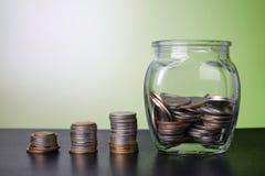 Bunt av pengar - mynt i den glass kruset - sparande pengarbegrepp arkivbilder