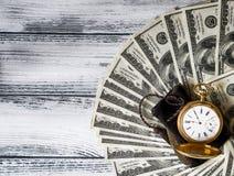 Bunt av pengardollar som ut läggas som en fan med den antika guld- klockan Arkivbilder