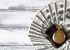 Bunt av pengardollar som ut läggas som en fan med den antika guld- klockan på vit wood bakgrund Arkivbild
