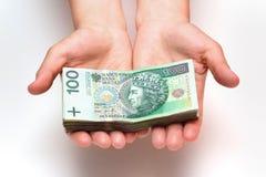 Bunt av polska sedlar i händer Arkivfoto