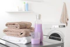 Bunt av rena handdukar och tvättmedel på tabellen arkivfoto