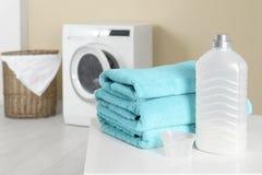 Bunt av rena handdukar och tvättmedel på tabellen royaltyfri fotografi