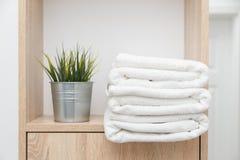 Bunt av rena handdukar på hylla med gräsplaner i hink royaltyfria foton
