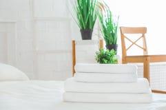 Bunt av rena handdukar på vit säng i rum Utrymme f?r text arkivfoto