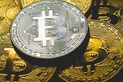 Bunt av silverbitcoins med guld- bakgrund med ett enkelt mynt som vänder mot kameran i skarp fokus med skuggning på symbol Royaltyfria Bilder