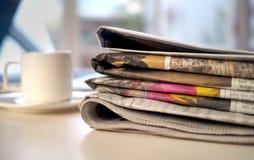 Bunt av tidningar med den kaffekoppen och datoren arkivbilder