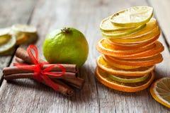 Bunt av torkade apelsin- och citronskivor, limefrukt och kanelbruna pinnar arkivbild