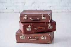Bunt av tre bruna retro resväskor på det vita golvet royaltyfri foto