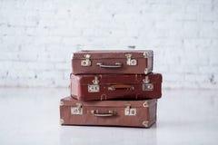 Bunt av tre bruna retro resväskor på det vita golvet fotografering för bildbyråer